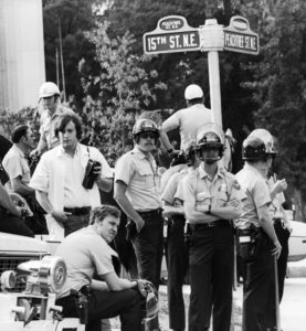 "Poleece. Fuzz, Da Pig. The Man. Here are Atlanta's finest gathered at Peachtree and 15th. They were a reserve force ready to rush down to Piedmont Park in case help was needed to quash yet another hippie musical rebellion antiwar thingy. Mayor Sam Massell tried to establish links with the hoard of longhaired dope-smoking anarchist hooligan fringe early in his administration. He even set up a police precinct on ""The Strip"" called ""The Pig Pen"" with a window mural by ""J.J. of L.A."" of Rich's-like pink pig wearing a patrolman's cap. The cops who worked the office were really cool."