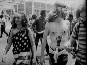 Flag wrapped, long haired, bandannaed and a little paranoid, this couple marches along Peachtree Street in a May, 1970 anti-war demonstration.